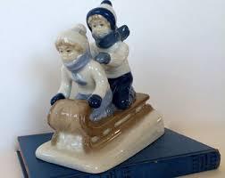 cabin decor lodge sled: ceramic figurines sledding children on sled statue sledding blues ceramics centerpiece christmas decoran winter lodge decor snow figurines