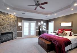 ceiling fan in bedroom. a luxurious master bedroom with soft carpet, french doors to patio, custom ceiling fan in r