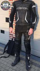 A photograph showing a slim biker wearing a two-piece leather racing suit  rated as Class AAA under EN 17092 and combined with premium sport motorcycle  boots certified as CE Level 2 -