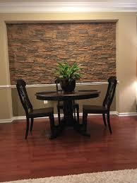Dining room accent wall created with stacked stone style panels.