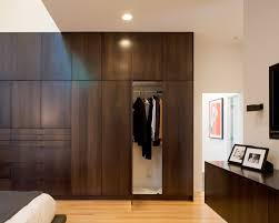 Modern reach-in closet idea in Kansas City with flat-panel cabinets and dark