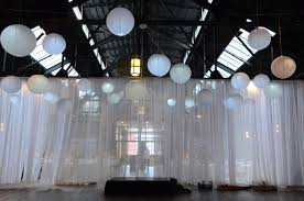 25 paper lanterns each with a decorative led light to provide a soft glow suspended over the ceremony with a white shear partitioning curtain