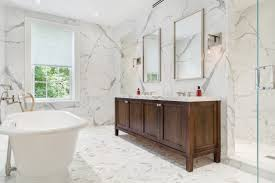 White marble bathroom with vanity, free standing tub and large shower