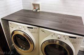 this dark wood look countertop not only adds function to our small laundry space it also makes it look so much more like the finished laundry room i had