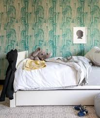clad in kelly wearstler crescent wallpaper this contemporary bedroom features a twin white lacquer bed with a trundle dressed in white and gray bedding and