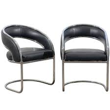 pair of rounded back chrome chairs in black leather for