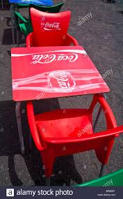 bright red plastic coca cola logo table and chairs at restaurant on the sea front at playa quemada lanzarote