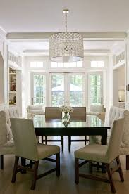 lovely square dining room with oly studio serena drum chandelier over glossy black square dining table surrounded by nailhead dining chairs and tufted