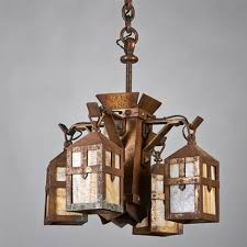 chandelier with central faceted shaft and four brackets each supporting a slag glass lantern by arts