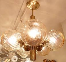 this mid century austrian chandelier with subtle honey amber hued swirling globes and rich clean lined
