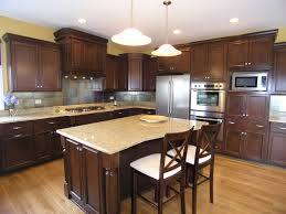 brown polihsed wooden kitchen cabinet and island with cream granite