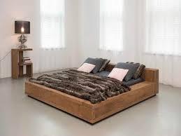 brown Teak Bed Frame with grey bedding set on pale green rug ...
