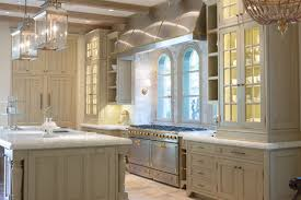 over stove lighting. sophisticated kitchen features glassfront china cabinets with custom lighting stacked atop tan painted farrow u0026 ball old white paired over stove