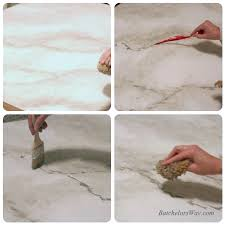 add the marble veins by dipping the tip of the feather into the darker gray paints and dragging and wiggling it across the countertop