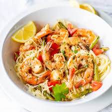 a bowl of shrimp scampi with angel hair pasta lemon wedges asparagus and tomatoes