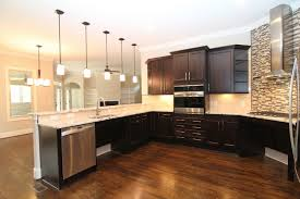 Get An Up Close View Of The Gas Range. A Stainless Steel Hood Is Backed By  A Linear Mini Tile Mosaic Pattern. The Tile Contains A Range Of Colors  Found In ...