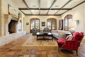 living room tile floor. mediterranean living room with carpet, high ceiling, built-in bookshelf, exposed beam tile floor m