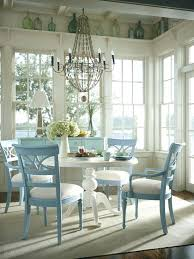 round dining room furniture with white table and light blue chairs on beige rug dark wood