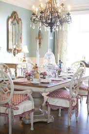french country dining room ideas with crystal chandelier over wooden table and white chair with pink