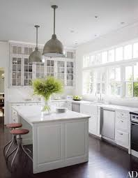urban archaeology lights are suspended above the kitchen island in decorator victoria hagans connecticut house the