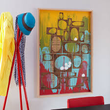 frame the artwork and add two hangers 1 inch from the top of the frame and hang