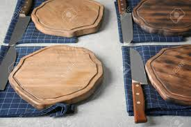 Knives And Napkins With Wooden Boards On Kitchen Table Cooking