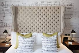 Beautiful bedroom features beige velvet wingback headboard on sheet music  wallpaper accented with crisp white hotel bedding, chartreuse pillows and  sheet ...