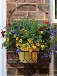 vibrant pots of yellow million bells red verbena and blue lobelia provide splashes of
