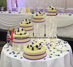top of cake covered in white maltesers white roses on top of cake with hints of purple spiral style wedding cake placed on crystal stand