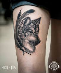 тату волка с перьями на бедре фото татуировок