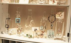 Different sized bottles used to hang necklaces, more creative jewelry  display ideas.