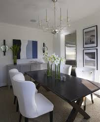 chic coastal dining room with visual comfort george ii chandelier over glossy espresso brown x base dining table with white modern wingback tufted dining