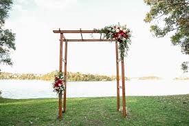 wooden wedding arch decorated with flowers next to a lake