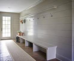 gray mudroom boasts gray shiplap walls lined with a shelf ledge and a row of hooks over an extra long bench alongside a bound herringbone sisal runner