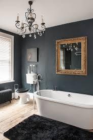black bathroom gold mirror and delicate chandelier in dark bathroom