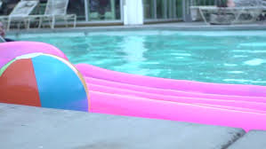swimming pool beach ball background. Slow Motion Shot Of Colorful Beach Ball And Floating Raft In A Swimming Pool  With Boy Background