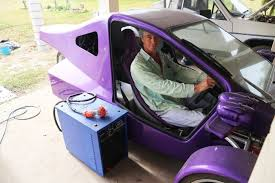 a man sits inside a purple three wheeled trike