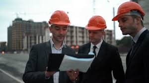Three Young successful architects in orange helmets and suits with blueprint