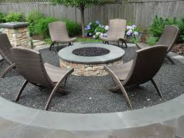 a round masonry gas fired fire pit clad in natural stone it sits