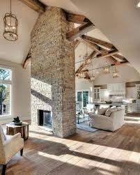 high ceiling lighting. brickstone statement fireplace wood beams unique light fixtures throughout open concept high ceilings larger opening and on both sides ceiling lighting