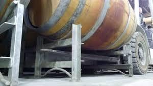 storage oak wine barrels. Wine Production And Bottling Area In Cellar Featuring Forklift Transport Rows Of Oak Storage Barrels