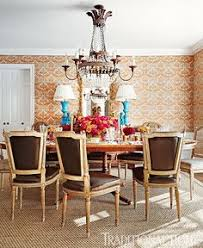 a chandelier sparkles above the antique gany table in the cheerful dining room photo