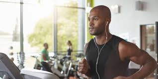 man in a gym running on a treadmill with head phones in