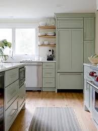 beautiful kitchen features sage green cabinets paired with white quartz countertops