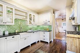 cream wall mounted kitchen cabinet white kitchen drawers green tile backsplash wooden floor under cabinet range hood
