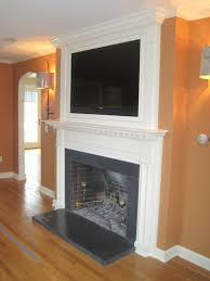 recessed tv behind a custom built frame over the fireplace