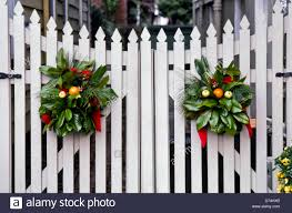 Christmas decorations of greenery wreaths decorate on white picket fence  gate, Portsmouth, Virginia, USA