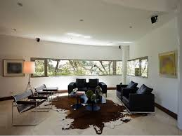 brown cowhide rug with black sofa for living room decorating ideas