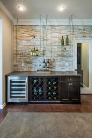 create a dynamic home bar with floating glass shelves that contrast the light stone accent wall
