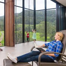 woman on chair watching children in enclosed patio fitted with crimsafe security screens